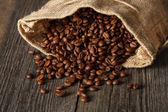 Coffee bag with coffee beans on wooden surface — Stock Photo