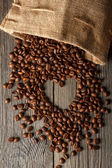 Heart shape made from coffee beans on wooden texture or table with coffee bag. — Stock Photo