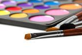 Primer plano de pinceles de maquillaje con la paleta de colores de sombra de ojos. — Foto de Stock