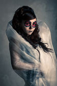 Portrait of young woman with sugar skull make-up . Dramatic lighting. — Stock Photo