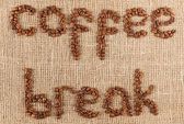 Coffee brake title laid out from coffee beans on a burlap pattern. — Stock Photo