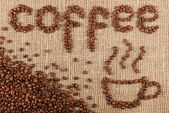 Coffee title with cup laid out from coffee beans on a burlap pattern. — Stok fotoğraf