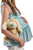 Schwangere junge frau holding plüsch hundespielzeug — Stockfoto