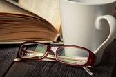 Taza de té caliente, libro, anteojos — Foto de Stock