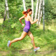 Beautiful young woman runner in a green forest. Moton blur — Stock Photo
