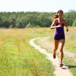 Stock Photo: Beautiful young woman running outdoors