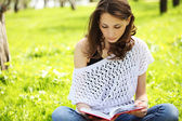 Image of young beautiful woman in summer park reading a book — Stock Photo