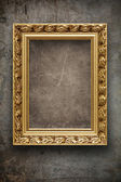 Dark, grungy wall with gold frame — Stock Photo