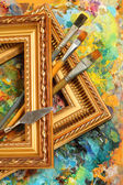 Image of artist's palette, paintbrushes and art frames — Stock Photo
