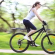 Pretty woman with bicycle in a green park — Stock Photo