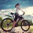 Pretty womwith bicycle in park — Stock Photo #31736113