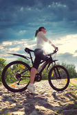 Pretty woman with bicycle in a park — Stock Photo