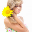 Beautiful girl with a flower of sunflower in her hair — Stock Photo