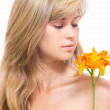 Young woman with bare shoulders looks at a lily in her hands — Foto Stock