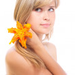 Cute girl with a flower of lily in her hair — Stock Photo
