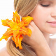 Beautiful girl with a flower of lily in her hair — Stock Photo #29352675