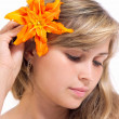Young girl with bare shoulders and lily in her hair — Stock Photo #29352705