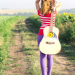 Girl walking along the road with a guitar over  shoulder — Stock Photo
