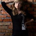 Portrait of beautiful girl standing near red brick wall — Stock Photo