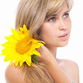 Cute girl with a flower of sunflower in her hair — Stok fotoğraf