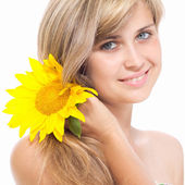 Smiling girl with a flower of sunflower in her hair — ストック写真