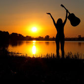 Silhouette of a happy girl with a guitar on a sunrise — Stock Photo