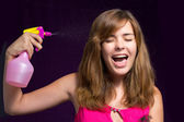 Girl tired of cleaning the house, and she uses a spray on yourself — Stock Photo
