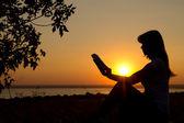 日没時の手で本を持つ少女のシルエット — ストック写真