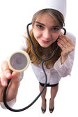 Young woman doctor with phonendoscope examines — Stock Photo