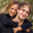 Happy young attractive couple portrait, smiling in outdoor environment — Stock Photo