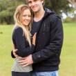 Cheerful young couple hugging and smiling in a park — Stock Photo