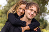 Happy young attractive couple portrait, smiling in outdoor environment — Stockfoto