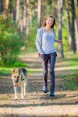 Femme qui marche en plein air souriant avec chien — Photo
