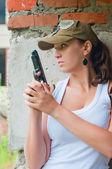 Frau in gap mit pistole versteckt über mauer — Stockfoto
