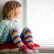 Curious child looking out window — Stock Photo