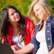 Two women friends outdoors with laptop — Stock Photo