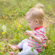 Baby sitting on grass in field — Stock Photo
