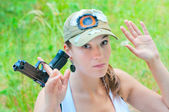 Woman hands raised with gun — Stock Photo