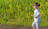 Pequena menina em pé no campo — Foto Stock