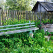 Rural landscape with bench and a well — Stock Photo #39370119