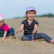 Two little sisters playing in the sand on the beach — Stock Photo