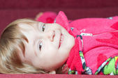 Smiling little girl on sofa — Stock Photo