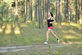 Woman jogging in forest — Stock Photo