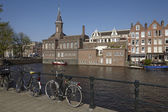 Amsterdam, Netherlands - Old building with tower at a canal — Stock Photo