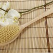 Stock Photo: Bath brush on mat of bamboo and orchid