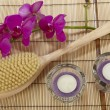 Stock Photo: Bath brush, orchid and tealights on mat of bamboo