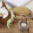 Bath brush, rolled towels, tealight and orchids — Stock Photo #39319477
