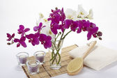 Wellness - Bath brush, towel, orchids and tealights — Stock Photo
