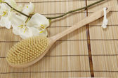 Bath brush on a mat of bamboo and an orchid — Zdjęcie stockowe