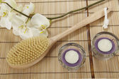Bath brush, orchid and tealights on a mat of bamboo — Stock fotografie